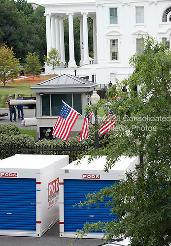 Storage pods on West Executive Avenue outside the White House West Wing in Washington, DC as it is undergoing renovations while United States President Donald J. Trump is vacationing in Bedminster, New Jersey on Friday, August 11, 2017.  Workers carrying carpet can be seen in the center left background of the photo.<br /> Credit: Ron Sachs / CNP