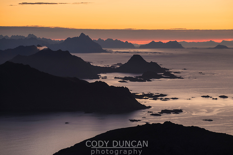 Mountains and fjords silhouette against sunrise, Lofoten Islands, Norway