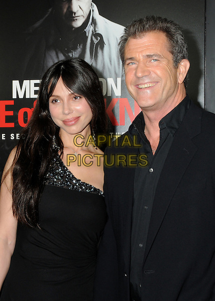 "OKSANA GRIGORIEVA & MEL GIBSON.Attending the ""Edge of Darkness"" Los Angeles Premiere held at Grauman's Chinese Theatre, Hollywood, California, USA, 26th January 2010..arrivals half length dress suit jacket   black shirt one shoulder  couple smiling beaded jewel encrusted embellished  .CAP/ADM/BP.©Byron Purvis/AdMedia/Capital Pictures."