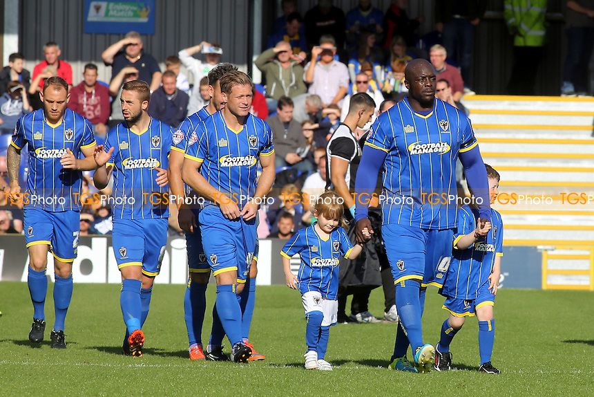 Crowd favourite, Adebayo Akinfenwa, walks onto the pitch with the AFC Wimbledon mascots - AFC Wimbledon vs Bury - Sky Bet League Two Football at Kingsmeadow Stadium, Kingston upon Thames, Surrey - 11/10/14 - MANDATORY CREDIT: Paul Dennis/TGSPHOTO - Self billing applies where appropriate - contact@tgsphoto.co.uk - NO UNPAID USE