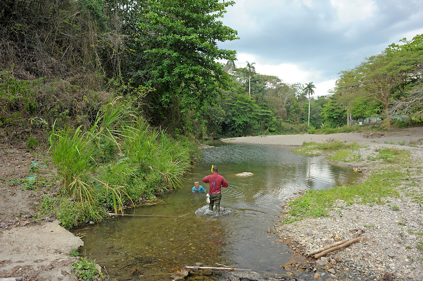 A man and a boy fish with snorkels and masks in a shallow creek high in the Escambray Mountains near Trinidad, Cuba. MARK TAYLOR GALLERY