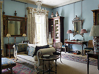 The sitting room is decorated in a cool blue with traditional furnishings. At the window are curtains in Hardwick Green by Robert Kime for Chelsea Textiles and large ceramic jars sit atop the tall bookcase.