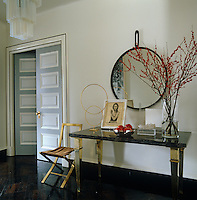 Double doors painted different shades of grey lead into the elegantly furnished entrance hall