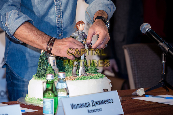 Antonio Banderas &amp; cake <br /> &quot;Justin and the Knights of Valour&quot; photocall, Moscow, Russia, UK, October 3rd 2013.<br /> hands denim shirt cake icing <br /> CAP/PER<br /> &copy;PersonaStars/CapitalPictures