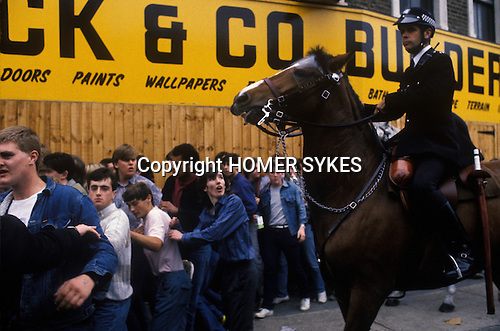 Arsenal football fans after a game, police crowd control on horseback. London. UK