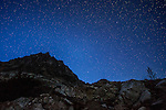 A shooting star streaks by Black Peak in Washington's North Cascade Mountain range on a clear, starry night in the fall.