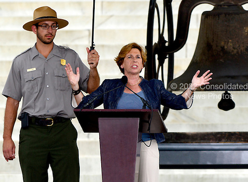 Randi Weingarten, president of the American Federation of Teachers,  makes remarks as a U.S. Park Police officer holds an umbrella to shield her from the rain at the Let Freedom Ring ceremony on the steps of the Lincoln Memorial to commemorate the 50th Anniversary of the March on Washington for Jobs and Freedom.<br /> Credit: Ron Sachs / CNP