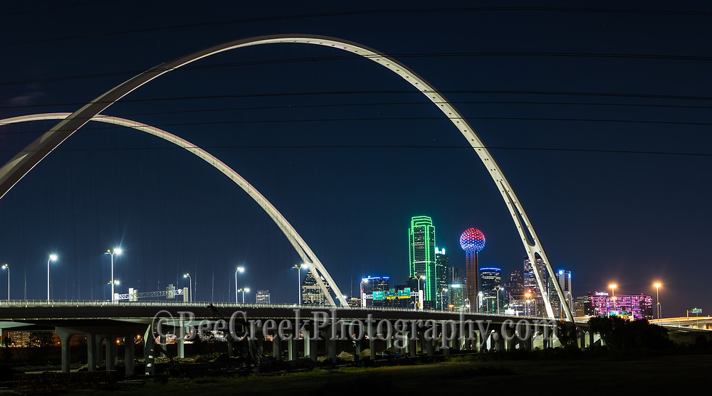 The new Margaret McDermott Bridge in downtown Dallas with skyline after dark. This is a steel bridge suspended with two arches over the Trinity River previously IH30 and is part of the Trinity project partially designed by Santiago Calatrava. This bridge is also designed to accomodate a pedestrian and bike path to join the the area other hike and bike trails. It was a night view from here at night.