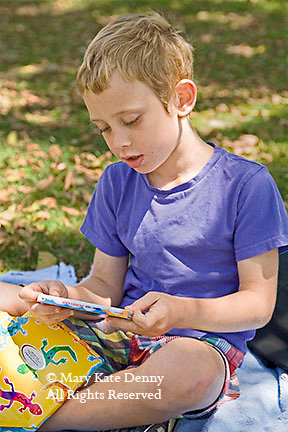 Elementary age male child sits in park opening his gift of a CD