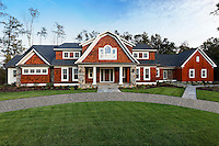 Traditional shingled mansion with palladium window, columned gambrel roofed entry and attached barn style garage and circular pebblestone paved driveway.