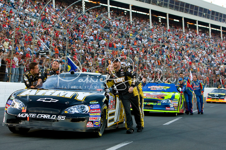 Pit crews push their cars to the starting position in the Bank of America 500 NASCAR race at Lowes's Motor Speedway in Concord, NC.