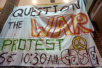 Large banner made of sheets containing peace symbol and reading: Question The War, Protest.