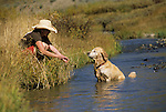 A young woman plays with her dog near Crested Butte, Colorado.