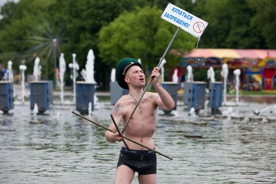 "Moscow, Russia, 28/05/2010..A member of the Russian Border Troops in a Gorky park lake waves a sign saying ""no swimming"" as the regiment celebrated their annual holiday.."
