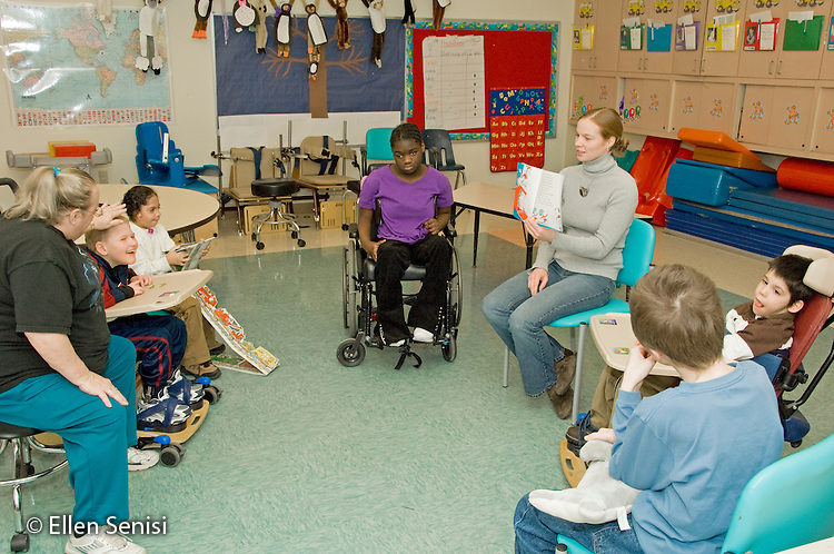 MR / Albany.Langan School at Center for Disability Services (private nonprofit disability services).Upper elementary classroom/Day Program.Teaching assistant reads book to group of students in special education classroom. Students conditions include Duchenne muscular dystrophy, Pierre Robin Sequence, and cerebral palsy..MR: AH-cfds.© Ellen B. Senisi