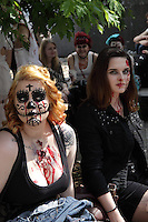 2 women participating in the Zombie Walk in Prague Europe, sitting on a bench, one wearing a sleeveles blouse, with blood down her chest, and painted with black laces in the face, the other with dark hair wearing dark clothes, with blood in her face
