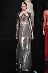 "Model walks runway in a metallic silver dress with black guipure lace and pewter embroidered from the Reem Acra Fall 2016 ""The Secret World of The Femme Fatale"" collection, at NYFW: The Shows Fall 2016, during New York Fashion Week Fall 2016."