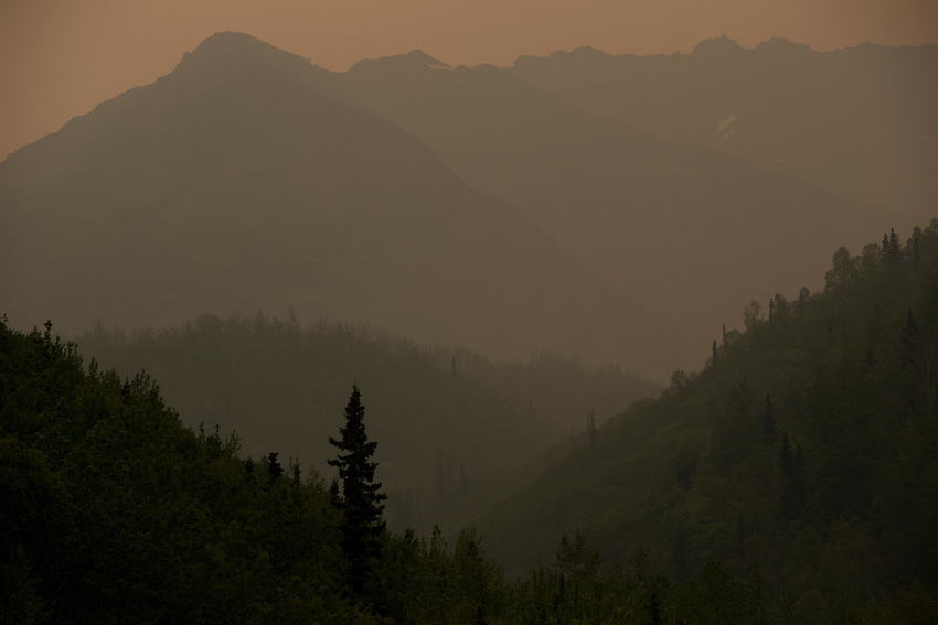 Smoke and haze from the Funny River Fire on the Kenai Penninsula settles over the Chugach Mountains near Eagle River, Alaska. The fire burned more than 195,000 acres.