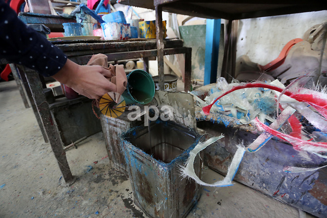"Palestinian men work on the manufacture and maintenance of the swings ""amusement games"" at al-salam factory in the Zeitoun neighborhood, in Gaza city, on November 26, 2016. Israeli occupation prevented of the introduction of large amounts of material ""Fiber Glass"" which makes them the swings, leading to high prices and stop a large number of factories for work. Photo by Mohammed Asad"
