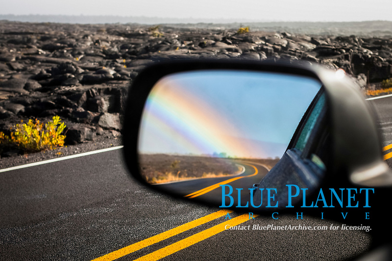 rainbow in the side mirror of car, travelling after the rain at Hawaii Volcanoes National Park, Big Island, Hawaii, USA