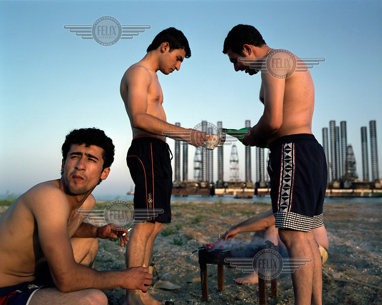 Young men smoke and drink as they have a barbecue on one of Baku's city beaches, with oil rigs in the background.