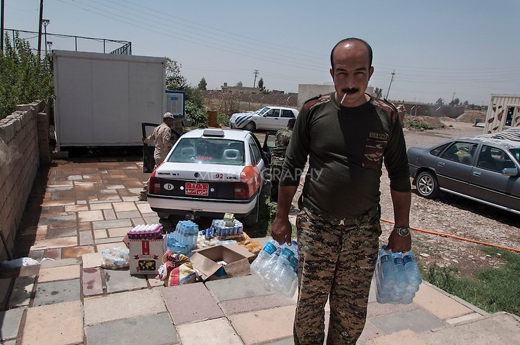 21/07/14  Iraq -- Daquq, Iraq -- A Peshemrga brings water bottles donated by local population at the base in Daquq.