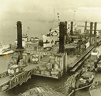 BNPS.co.uk (01202 558833)<br /> Pic: MitchellsAuctionHouse/BNPS<br /> <br /> PICTURED: LST Spud pierhead assembly showing clearing casualties at the same time as army vehicles being discharged from landing craft Arromanches.<br /> <br /> The fascinating archive of one of the engineers who designed the Mulberry Harbours which were installed off the Normandy coast following the D-Day landings has come to light.<br /> <br /> Colonel Vassal Charles Steer-Webster OBE helped create the giant, floating artificial harbours which protected anchored supply ships from German attacks.<br /> <br /> They were built in the dry docks on The Thames and Clyde and pulled across the channel by tugs before being hastily assembled.<br /> <br /> Col Steer-Webster was in almost daily contact with Churchill during their development ahead of June 6, 1944. Now, his personal effects, including a letter of thanks from Winston Churchill, are being sold by his nephew with Mitchells Auctioneers, of Cockermouth, Cumbria. <br /> <br /> The archive, which is expected to fetch £15,000, also features 150 photos showing Mulberry B's construction and use, as well as his medals.