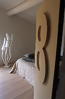 A door bearing a large figure eight opens on to a simply furnished bedroom which features a lamp by David Emery