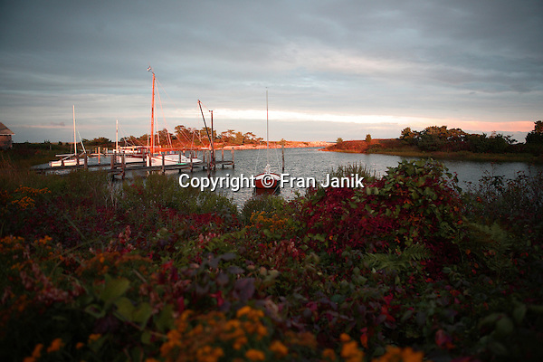 At dusk, several sailboats rest at their moorings in a quiet Island cove in the town of Oaks Bluff on the Island of Martha's Vineyard. The Island is located off the coast of Massachusetts, to the south of Cape Cod. Settled by the English in 1642, it became an important center of fishing and whailing during the 18th and 19th centuries. The harbor is seen on an October day at sunset.