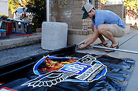 NWA Media/DAVID GOTTSCHALK - 9/22/14 - Colby Jordan, with Southern Trend Clothing, helps affix a banner to one of five official Bikes, Blues & BBQ merchandise tents on Dickson Street Monday September 22, 2014 in Fayetteville. This is the 15th year for the motorcycle rally that runs from September 24 through September 27 with music, vendors, activities and events taking place throughout Fayetteville and Northwest Arkansas.