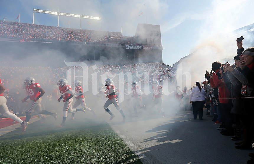The Ohio State football team runs on to the field before the NCAA football game against Michigan at Ohio Stadium on Saturday, November 29, 2014. (Columbus Dispatch photo by Jonathan Quilter)