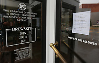 The front door of Brewski's has additional signage March 19, 2020, telling patrons that the establishment is closed because of potential health concerns with the covid-19 virus.  Restaurants, bars businesses in the city of Fayetteville are making adjustments because of the spread of covid-19. Check out nwaonline.com/200322Daily/ and nwadg.com/photos for a photo gallery.<br /> (NWA Democrat-Gazette/David Gottschalk)