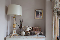 A gilded lamp stands on a chest in an alcove in the living room. A photograph of Ryan and her daughter hangs on the wall above