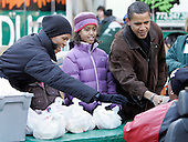 Chicago, IL - November 26, 2008 -- United States President-elect Barack Obama, right, daughter Malia, center and wife Michelle greet people at they pass out food at St. Columbanus Parrish and School Wednesday, November 26, 2008, in Chicago, Illinois. .Credit: Frank Polich - Pool via CNP