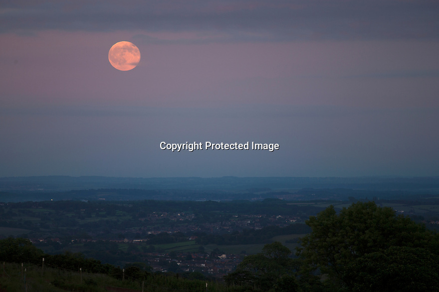 20/06/16 <br /> <br /> On the shortest night of the year, photographers take shots of the setting sun behind Alport Stone, while a 'Strawberry Moon' rises behind them above Alport Height near Wirksworth, Derbyshire. The next time this rare summer moon, which some say gets its name as it marks the start of the strawberry picking season,  will be seen on the night of the summer solstice will be in 46 years time.<br /> <br /> All Rights Reserved F Stop Press Ltd +44 (0)1335 418365