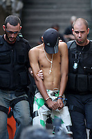 Rio de janeiro State Police Police (PMERJ) escort a prisoner down a stairway from a slum where a shootout took place about 3 hours earlier in Rio de Janeiro, Brazil, Oct. 21, 2009.