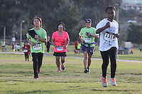 DeAnza Cove, Mission Bay, San Diego CA, USA.  Sunday, January 25 2015:  Participants in the 1-mile kids run portion of the Friends of Pacific Beach Schools (FOPBS) School Yard Dash arrive at the finish line.  The 2nd annual charity event which raises money for the six local schools in the Mission Bay Cluster, comprised of a 1-mile run for kids followed by a 5K run for all ages.  Besides parents, teachers, staff, students and siblings competitors from all over San Diego and abroad ran in the event.  All six schools in the Mission Bay cluster had information booths at the event for potential parents to meet and speak with staff and students.  Music was provided by local teenage band Rubber Band and the string ensemble from Crown Point Elementary School.