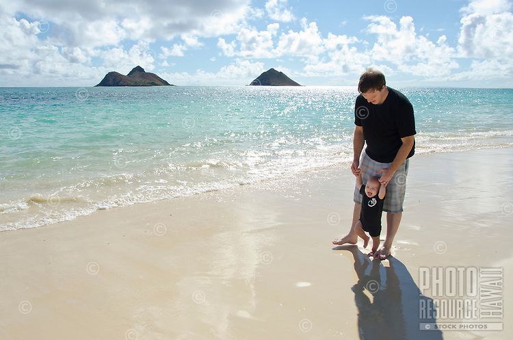 A father and son playing on Waimanalo Beach, O'ahu, with the Mokulua Islands in the distance.