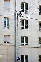 A proximite du centre-ville, persistence de lignes electriques aeriennes sur des immeubles recents