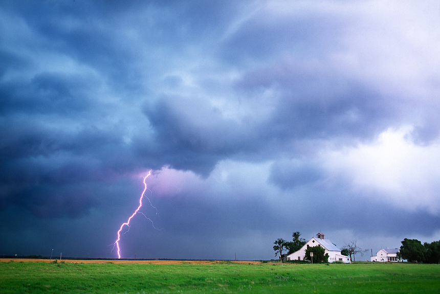 Cloud-to-ground lightning heralds the approach of severe thunderstorms to a farmstead in western Oklahoma in the spring.