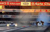 Nov 12, 2010; Pomona, CA, USA; NHRA funny car driver Ashley Force Hood (left) races alongside Paul Lee during qualifying for the Auto Club Finals at Auto Club Raceway at Pomona. Mandatory Credit: Mark J. Rebilas-