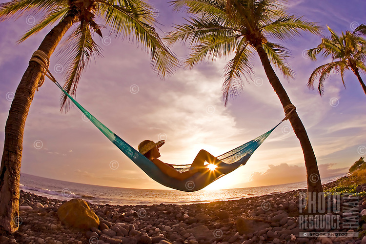 A girl with hat reclines in a hammock with a sunstar between her legs at Olowalu, Maui.