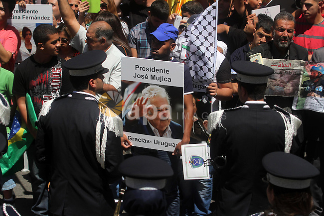 "Palestinians hold posters during a rally supporting South American countries, in the West Bank city of Ramallah, Monday, Aug. 11, 2014. During the war, Bolivia's president has declared Israel a ""terrorist state"" while South American countries, including Brazil, Chile, Ecuador and Peru, have recalled their ambassadors from Israel because of its operation in the Gaza Strip. Photo by Shadi Hatem"