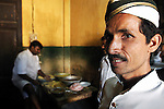 A waiter stands in the kitchen of a cafe/restaurant in Kolkata, India