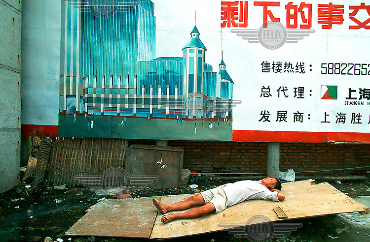 Mark Henley/Panos Pictures..China, Shanghai, Pudong..Contrast. Man sleeping on board under advertising for new development.