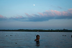 A young monk takes a dip, at the foot of the Athawkarma Magyi Monastery as the sun sets, and the moon rises! The monastery lies at the mouth of a river in the Ayeyarwaddy Delta.