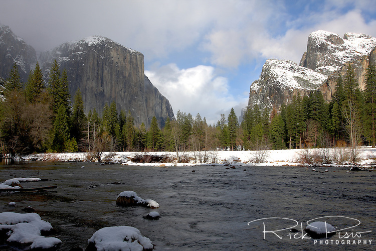 Snow lines the Merced River along with El Capitan and The Three Brothers in Yosemite National Park.