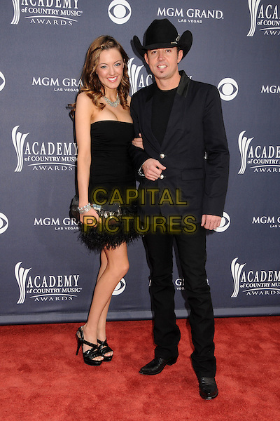GUEST & TROY OLSEN .46th Annual Academy of Country Music Awards - Arrivals held at the MGM Grand Garden Arena, Las Vegas, Nevada, USA, 3rd April 2011..full length dress black suit cowboy hat jacket  feather trim clutch bag sandals strapless .CAP/ADM/BP.©Byron Purvis/AdMedia/Capital Pictures.