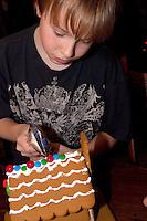 Boy age 10 decorating a Christmas gingerbread house. St Paul Minnesota USA