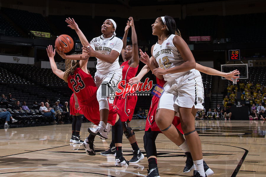 Destini Walker (1) of the Wake Forest Demon Deacons drives to the basket between two Davidson Wildcats defenders during second half action at the LJVM Coliseum on November 17, 2015 in Winston-Salem, North Carolina.  The Demon Deacons defeated the Wildcats 77-58.  (Brian Westerholt/Sports On Film)